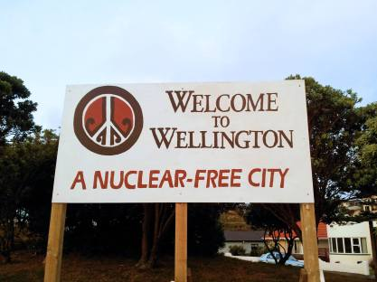 "Sign reading""Welcome to Wellington: A nuclear-free city"" and a peace symbol with koru styling"