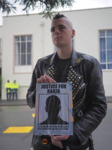 Protestor holds up a picture of Rakib, an asylum seeker who committed suicide on Nauru after asking for mental health help